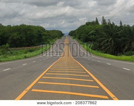 Long hilly road passes through green countryside with cloundy sky.
