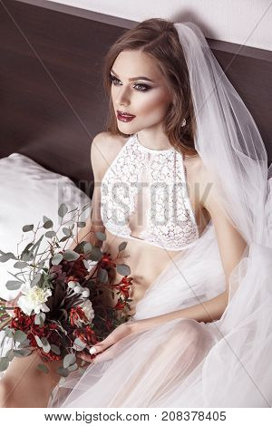 View From Above Beautiful Brunette Woman In Bridal Underwear. Girl Sitting In Bed, Holding Flowers A