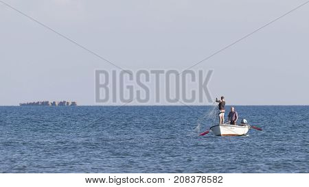 Ulcinj riviera - October 1 2017: Two fishermen fishing with nets from boats and Guri i island of Girona in the distance on the Great Montenegrin beach Ulcinj Riviera Montenegro