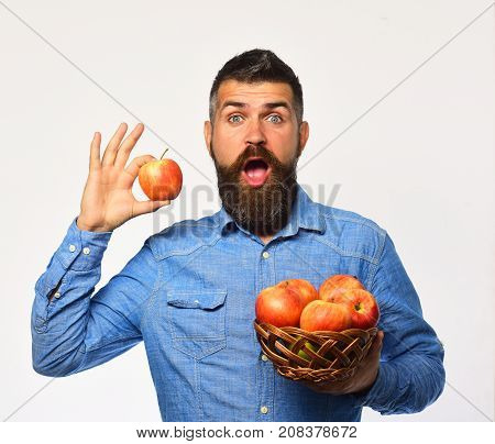 Farmer With Surprised Face Holds Red Apple.