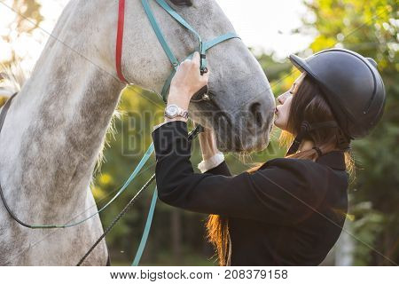 Young brunette beauty girl gently kissing her horse in the park