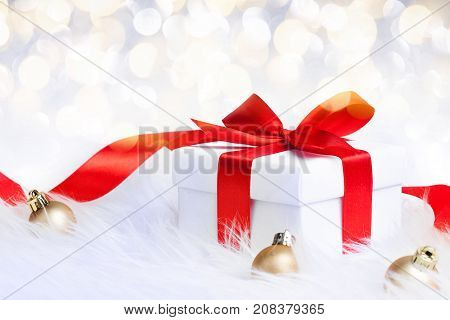 Gift box with red ribbon bow and christmas ball on glitter background. xmas card