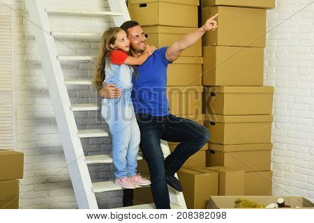 Daughter And Father Sit On White Ladder Near Boxes