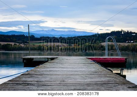 walkway in a lake with forest in the background