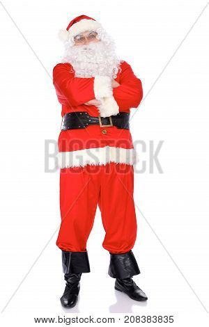 Santa Claus standing with ars crossed, isolated on white background. Full length portrait.