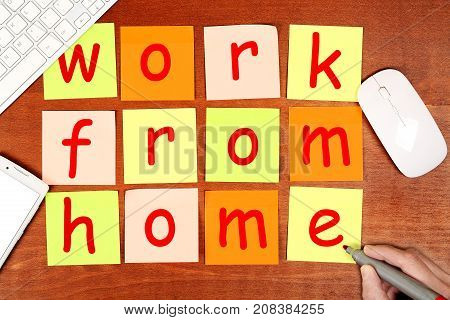 hand writing work from home on adhesive notes top view of modern desk