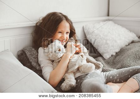 happy kid girl playing with teddy bears in her room sitting on bed in pajama