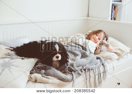 happy kid girl waking up in the morning in her bedroom with dog in bed
