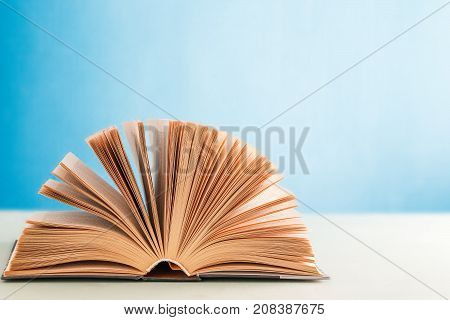 An Open Hardcover Book On A Blue Background