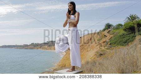 Stylish young model in white outfit standing on one leg and meditating with eyes closed on background of ocean and cliffs.
