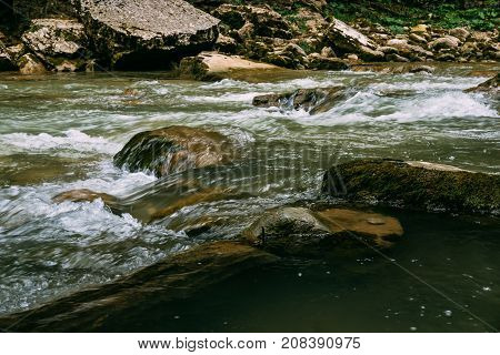 Tranquil mountain river stream landscape, flowing water, toned