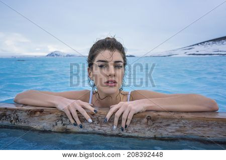 Beautiful girl in a white swimsuit holds a wooden crossbeam in the geothermal pool on the background of snow mountains and cloudy sky outdoors in Iceland. She looks into the camera with parted lips.