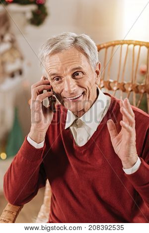 Keep smiling. Attractive grey-haired man wrinkling forehead and looking aside while actively gesticulating