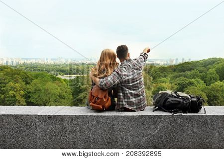 Happy young tourists admiring beautiful view outdoors