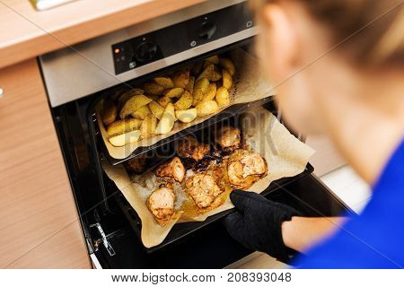 woman preparing potatoes and chicken meat in oven at home kitchen