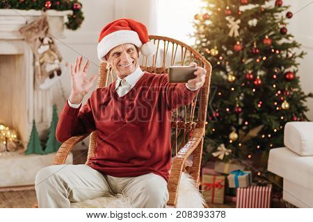 Watching you. Positive delighted man holding telephone in left hand and wearing Christmas hat while having party