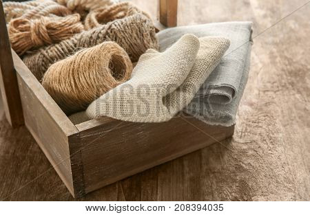 Hemp cloth and rope in crate on wooden background