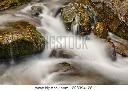 A beautiful view with silky water in a fast mountain river flowing among the stones with green moss in the mountains shot on a long exposure