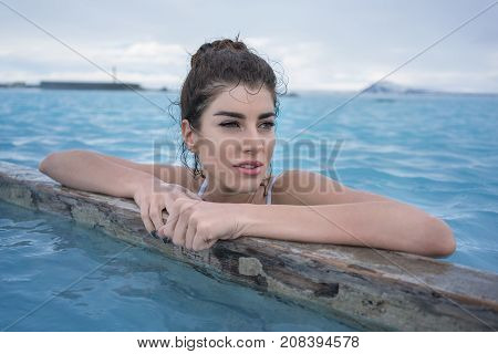 Hot girl in a white swimsuit holds her hands on a wooden crossbeam in the geothermal pool on the background of the cloudy sky outdoors in Iceland. She looks to the side with parted lips. Horizontal.