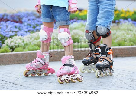 Active boy and girl rollerskating in park