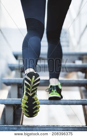 Medium shot of a woman jogging in a city. Shallow DOF focus on the shoe.