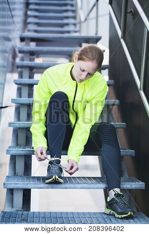 Sports in a city - woman sitting on metal stairs and tying her jogging shoe. Shallow DOF focus on the shoe.
