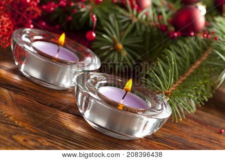 Candles And Christmas Decorations On Branch Of Spruce Tree