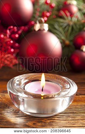 Candle and christmas baubles and tree on wooden table