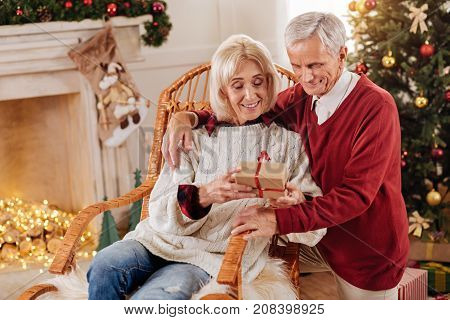Happy pensioners. Pretty woman keeping smile on her face and bowing head while looking at present