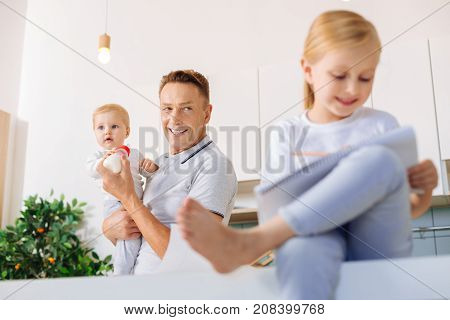 Be creative. Happy nice positive man smiling and looking at his daughter while encouraging her creativity