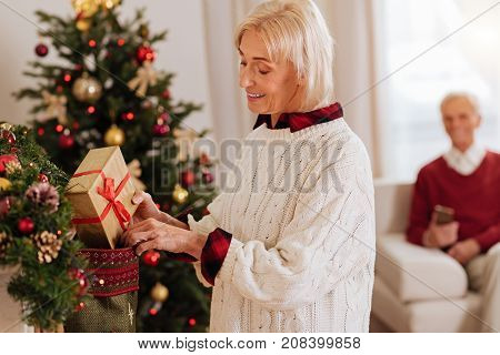 It is too big. Smiling woman bowing head and wearing cozy sweater while looking downwards