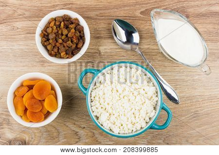 Bowls With Cottage Cheese, Dried Apricots, Raisins, Yogurt And Spoon