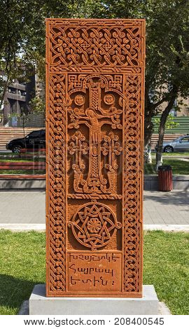 YEREVAN,ARMENIA - SEPTEMBER 24,2017: Khachkar the sacred stone cross in the historical center of Yerevan.It depicts sculpture of Jesus in the altar.Memorable inscription under it - in memory of him.