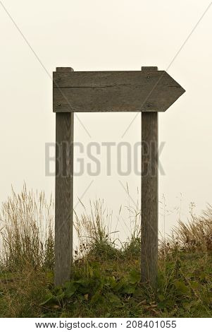 wooden signpost (without an inscription) standing in a fog