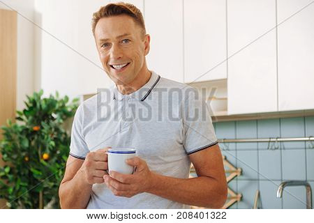 At the weekends. Happy delighted nice man smiling and drinking tea while resting at home during weekends