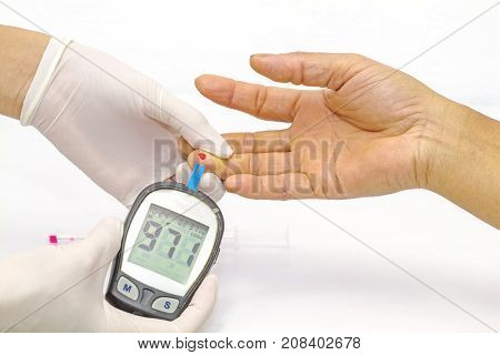 blood glucose meter the blood sugar value is measured on a finger by female doctor in white medical gloves