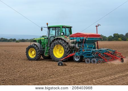 Karlovo Bulgaria - October 07: Modern John Deere tractor 6920 in the field. Farmer with tractor seeding - sowing crops at agricultural fields in autumn.