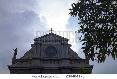 17 Sep 2017 Dumaguete Philippines - cathedral roof on cloudy sky background. Spectacular stormy clouds over dome. Sun on church cross. Catholic religion symbol. Philippines religious architecture
