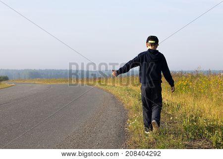 A boy in a dark sweatshirt hitchhiking on a field road on a clear summer day