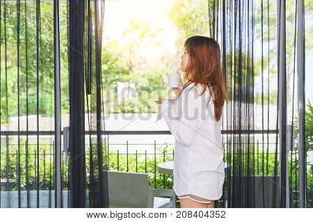 Young woman woke up and drinking coffee or tea under sunlight. Good morning.