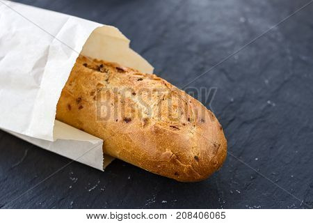 French appetizing fresh crispy fried golden baguette with onions in a craft package on a black graphite background.