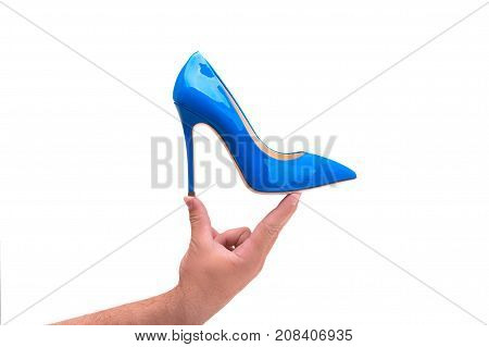 A man holds in his hand blue women's shoes with heels