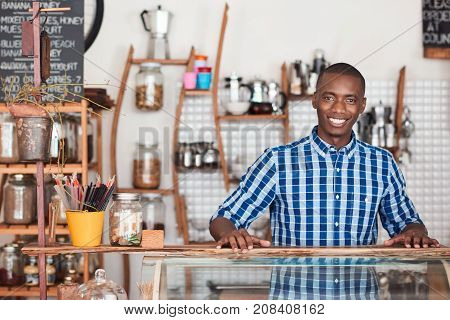 Portrait of a handsome young African entrepreneur smiling and standing welcomingly behind the order counter of his trendy cafe