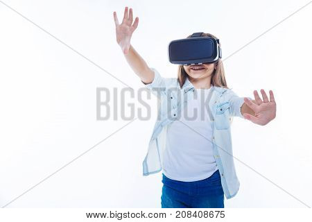 Virtual reality. Delighted cute positive girl wearing 3d glasses and smiling while being in virtual reality