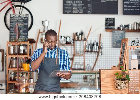 Young African entrepreneur talking on a cellphone and using a digital tablet while standing in his trendy cafe