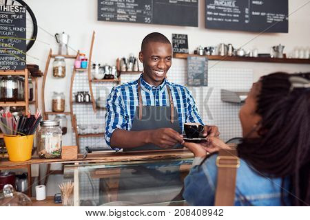 Smiling young African barista handing a cappuccino to a female customer while standing at the counter of a cafe