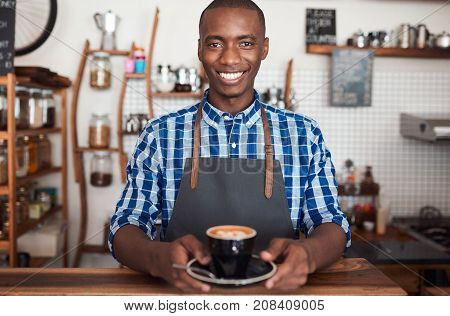 Portrait of a smiling African barista standing at the counter of a trendy cafe holding a fresh cup of cappuccino