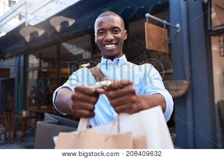 Portrait of a stylishly dressed young African man holding up shopping bags and smiling while out shopping in the city