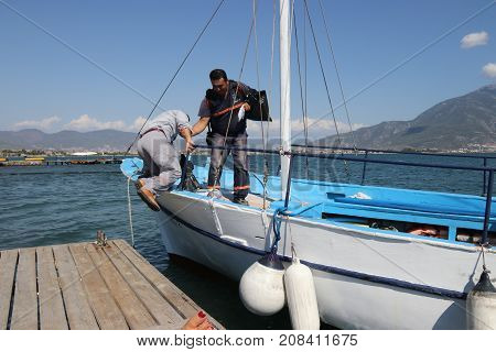 28TH JULY 2017,FETHIYE,TURKEY: A passenger climbing aboard a motor boat in the calm waters at calis,fethiye in turkey, 28th july 2017