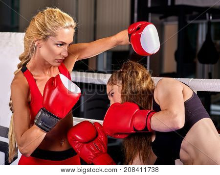 Two boxing women workout in fitness class. Sport exercise two female people. Boxer wearing red gloves to box in ring. athlete avoided the blow.